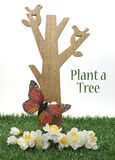 Happy Arbor Day, Plant a Tree greeting for last Friday in April, with wood tree, carved birds, butterfly and green grass Stock Images