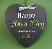 Happy Arbor Day, Plant a Tree, greeting message sign on heart shaped blackboard. Against a green background royalty free stock photo