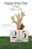 Happy Arbor Day, Plant a Tree greeting with shabby chic vintage wood calendar. For 25, last Friday in April, with wood tree, carved birds, butterfly, green stock image