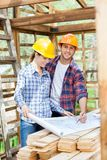 Happy Architect Examining Blueprint With Colleague Royalty Free Stock Images