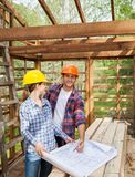 Happy Architect Examining Blueprint With Colleague Stock Images