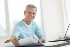 Happy Architect Holding Blueprint At Desk Royalty Free Stock Photo