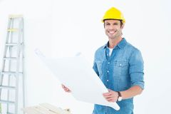 Happy architect holding blueprint in house. Portrait of happy male architect holding blueprint in house Royalty Free Stock Photo