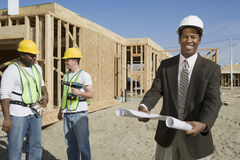 Happy Architect Holding Blueprint At Site. Portrait of a happy architect holding blueprint with workers standing in background Stock Photography