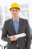 Happy architect holding blueprints looking at camera Royalty Free Stock Image