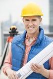 Happy Architect Holding Rolled Up Blueprint Stock Photo