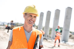 Happy architect looking away while holding clipboard at construction site Royalty Free Stock Photos