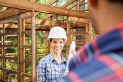 Happy Architect Looking At Colleague On. Happy female architect holding blueprint while looking at colleague on construction site Stock Photos
