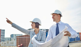 Happy architects with blueprint at building Royalty Free Stock Photo