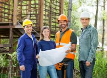 Happy Architects With Blueprint At Construction Stock Images