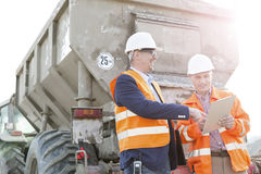 Happy architects discussing over clipboard by construction truck Stock Photography