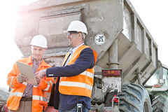 Happy architects discussing over clipboard by construction truck Stock Images