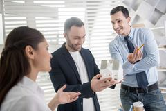 Happy architects discussing their project. Happy architects. Handsome glad young dark-haired architect smiling and holding a house miniature while his colleagues Stock Image