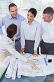 Happy architects interacting and analyzing plans together Royalty Free Stock Photos