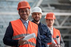 Happy architects are planning new project. Professional team. Low angle portrait of joyful young builders are standing together and looking ahead with smile Royalty Free Stock Photo