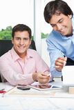 Happy Architects Working Together. Portrait of happy young male architect at desk with colleague standing beside Royalty Free Stock Photography