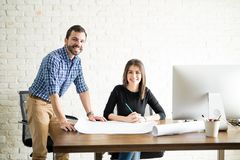 Two Hispanic architects working. Happy architects working together on a project at the office and drawing some building plans stock photo