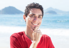 Happy argentinian guy at beach. Laughing at camera with ocean and blue sky in the background Stock Images