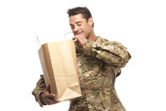 Happy army soldier looking into his shopping bag. Smiling army soldier looking at his grocery bag in front of white background Stock Photo