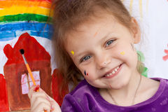 Happy artist. Portrait of a happy little girl with her painting Royalty Free Stock Photography
