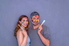 Happy artist couple. Coloring couple holding brushes smiling Stock Image