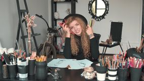 Artist with pencils. Happy artist with gorgeous fair hair sitting at the desk, holding lots of different coloured pencils, indoor portrait stock footage