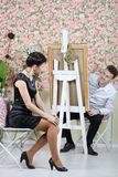 Happy artist peeks out from behind his easel on pretty woman Stock Photography
