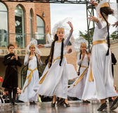 Happy artistic girls dancing in traditional Georgian white dresses during the City Day performance royalty free stock photography