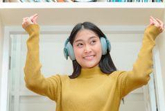 Asain woman in headphones enjoying music. Happy Asain woman in headphones enjoying music Stock Image