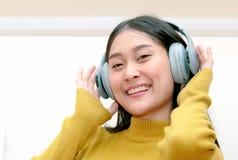 Asain woman in headphones enjoying music. Happy Asain woman in headphones enjoying music Stock Photography