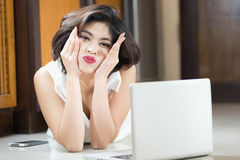 Happy asia woman Lying on Floor with Laptop at home Royalty Free Stock Photo