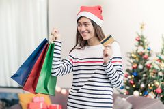 Happy Asia woman use credit card buy Christmas gift in shopping. Bag at home in party,Holiday online shopping royalty free stock image