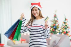 Happy Asia woman use credit card buy Christmas gift in shopping. Bag at home in party,Holiday online shopping stock photography