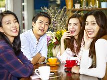Happy asian adults looking at camera smiling in coffee shop. Group of four happy asian young adults men and women looking at camera smiling while gathering in Stock Photography