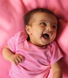 Happy asian baby girl in pink cloths. Happy asian (Indian) baby girl in pink cloths and pink background. Baby is three month old Royalty Free Stock Image