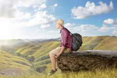 Happy asian backpacker with hat sitting at the edge cliff Royalty Free Stock Image