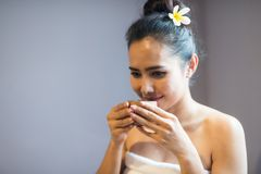 Woman smell hot green tea in spa. Happy Asian beautiful woman in white towel or bathrobe smell hot green tea before drinking in spa after body care treatment by Stock Images