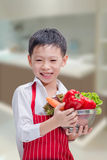 Happy Asian boy chef. With vegetable  in the kitchen Stock Images