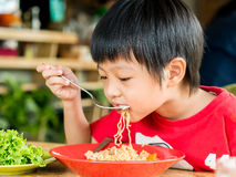 Happy Asian boy eating Royalty Free Stock Image