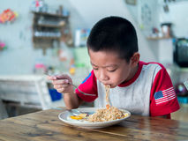 Happy Asian boy eating delicious noodle Royalty Free Stock Photos