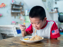 Happy Asian boy eating delicious noodle Stock Photos