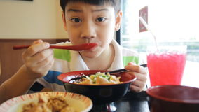 Happy asian boy eating japanese lunch set ,and looking camera . stock footage