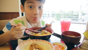 Happy asian boy eating japanese lunch set ,and looking camera . stock video footage