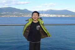 Happy Asian Boy with Eyes Closed Enjoying himself Visiting Vancouver's Inner Harbor Port  Royalty Free Stock Photography