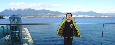Happy Asian Boy with Eyes Closed Enjoying himself Visiting Vancouver's Inner Harbor Port Stock Photography