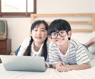 Happy asian boy and girl playing game in laptop lying on bed in bedroom in house,brother and sister using notebook do homework,