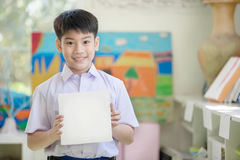 Happy asian boy hand holding blank paper board and looking at ca Stock Photography