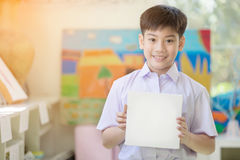 Happy asian boy hand holding blank paper board and looking at ca Stock Images