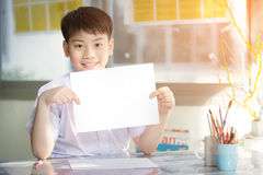Happy asian boy hand holding blank A4 paper sheet and looking at Stock Images