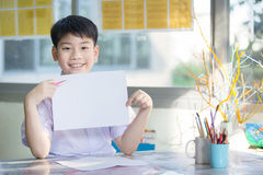 Happy asian boy hand holding blank A4 paper sheet and looking at Royalty Free Stock Photography